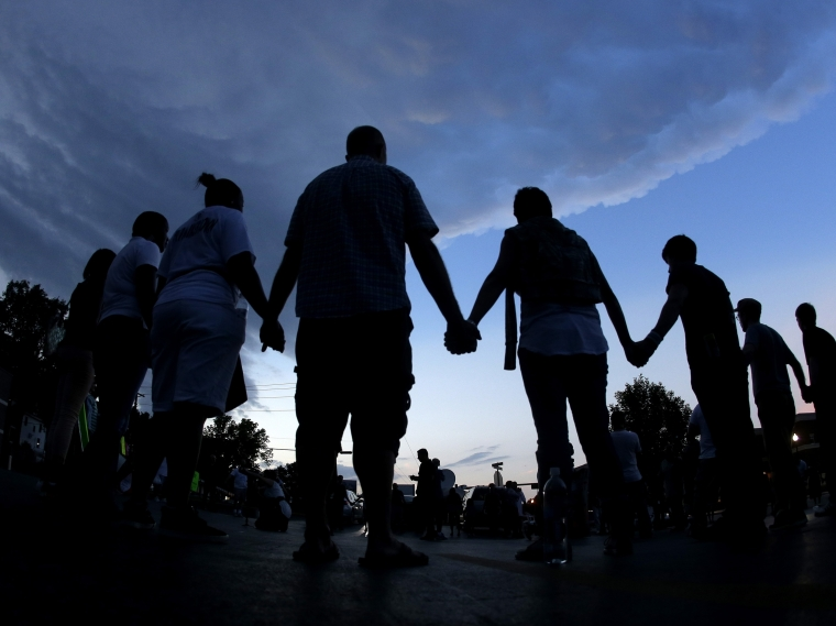 People stand in prayer Aug. 20 after a march in Ferguson, Mo., to protest the shooting of Michael Brown.